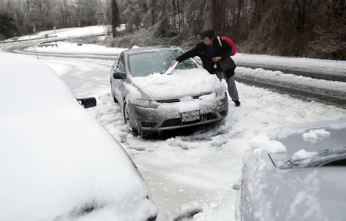 Daria Hester of Durham returns to her car on Edwards Mill Road, Thursday, Feb. 13, 2014 in Raleigh, N.C. Winter is taking one more shot at North Carolina. While the core of the system that brought snow, sleet and freezing rain to the state heads north toward Virginia on Thursday, parts of it were expected to dump even more snow on the state.