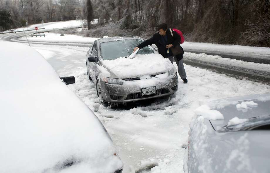 Daria Hester of Durham returns to her car on Edwards Mill Road, Thursday, Feb. 13, 2014 in Raleigh, N.C. Winter is taking one more shot at North Carolina. While the core of the system that brought snow, sleet and freezing rain to the state heads north toward Virginia on Thursday, parts of it were expected to dump even more snow on the state. Photo: Travis Long, Associated Press