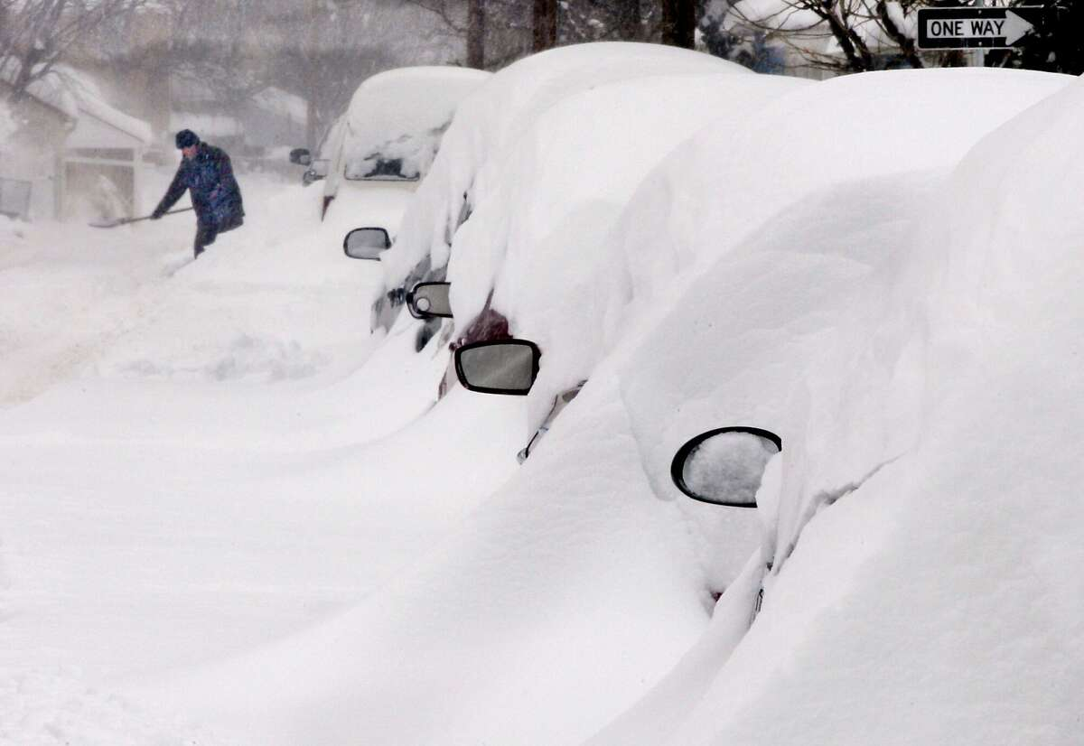 Snow covers a line of vehicles as a man digs out during a winter snow storm Thursday, Feb. 13, 2013, i n Winchester, Va.