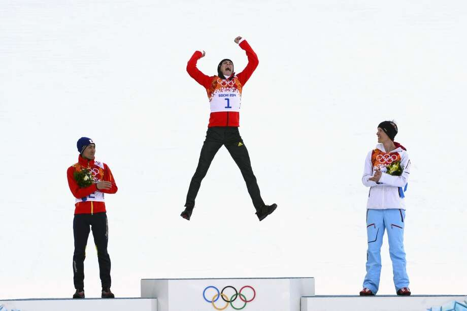 From left to right:- Silver medalist Japan's Akito Watabe, gold medalist Germany's Eric Frenzel and bronze medalist Norway's Magnus Krog celebrate on the podium during the Nordic Combined Individual NH / 10 km Flower Ceremony at the RusSki Gorki Jumping Center during the Sochi Winter Olympics on February 12, 2014 in Rosa Khutor near Sochi. Photo: JOHN MACDOUGALL, AFP/Getty Images