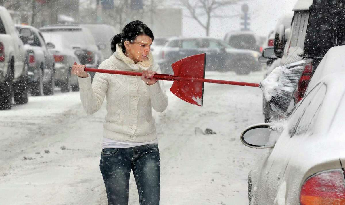 Stacy Marcelli clears snow from her car on Broadway Thursday Feb. 13, 2014, in Troy, NY. (John Carl D'Annibale / Times Union)