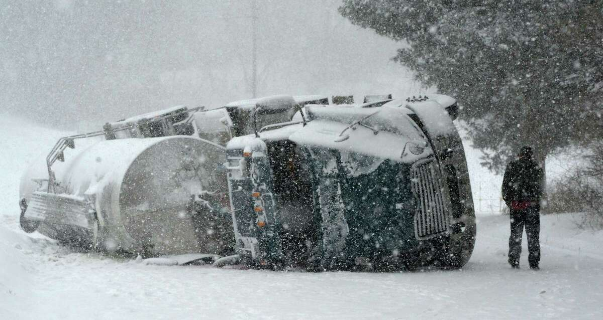 An overturned milk truck sits in the middle of Bridge Road Thursday afternoon Feb. 13, 2014, as the driver returns to his vehicle in Bethlehem, N.Y. after being interview by police at the scene. (Skip Dickstein / Times Union)