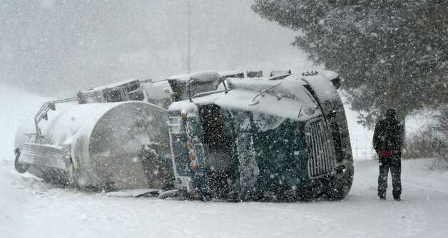 An overturned milk truck sits in the middle of Bridge Road Thursday afternoon Feb. 13, 2014, as the driver returns to his vehicle in Bethlehem, N.Y. after being interview by police at the scene.    (Skip Dickstein / Times Union) Photo: SKIP DICKSTEIN