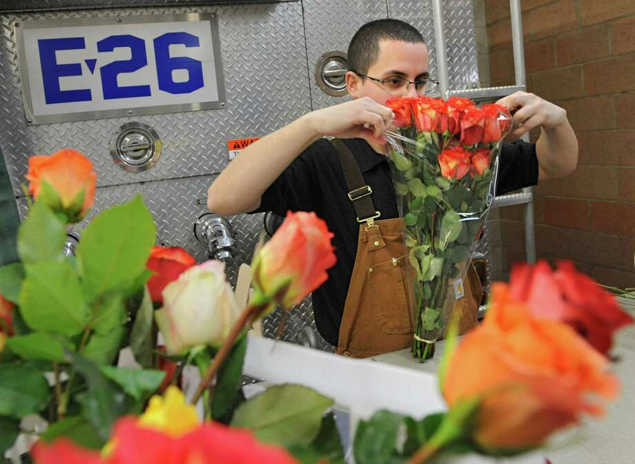 Firefighter Gregory Wilhelm of Guilderland arranges roses for a Valentine's Day fundraiser sale Thursday, Feb. 13, 2014, at the Guilderland Fire Department in Guilderland, N.Y.  (Lori Van Buren / Times Union) Photo: Lori Van Buren / 00025752A