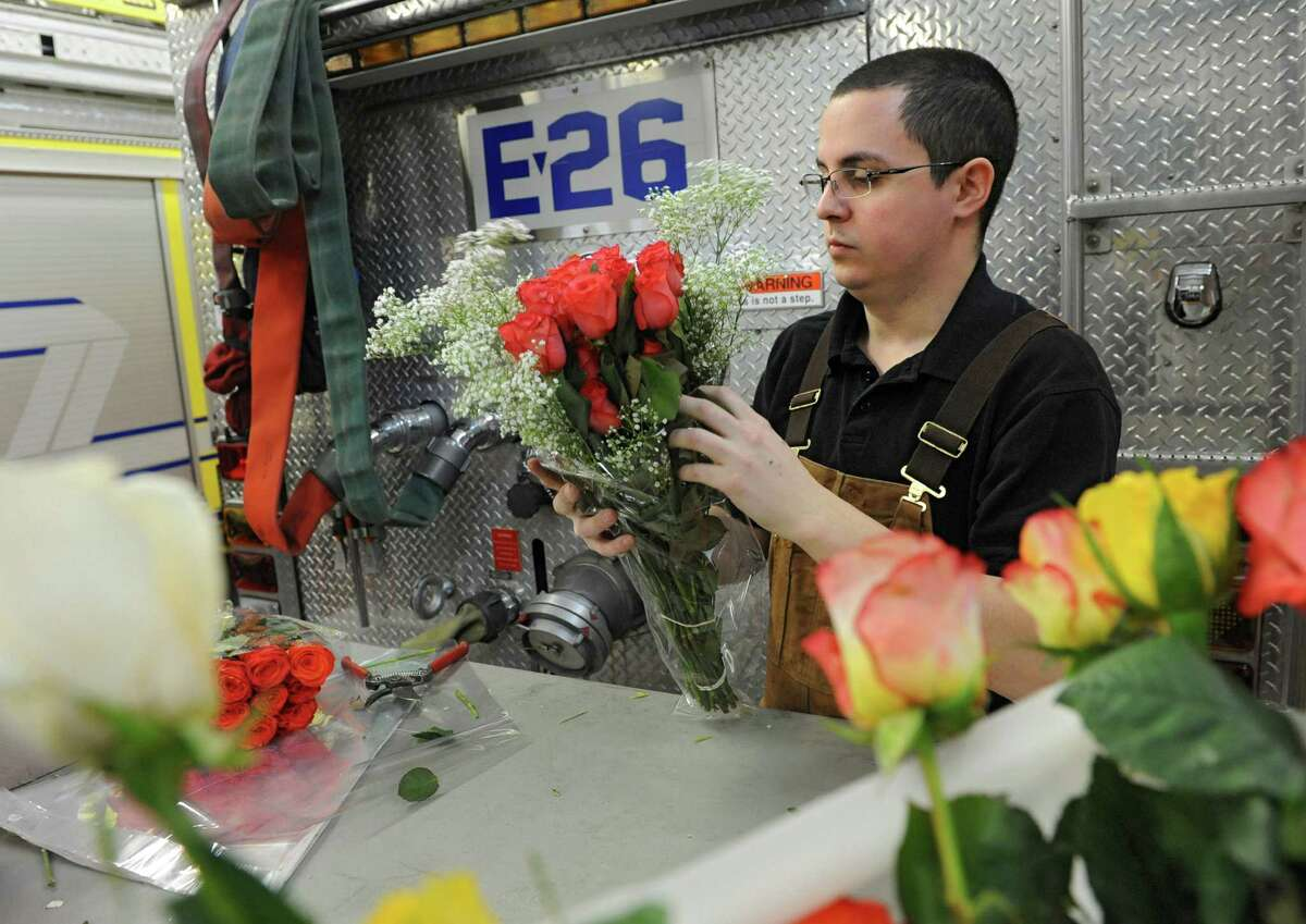 Firefighter Gregory Wilhelm of Guilderland arranges roses for a Valentine's Day fundraiser sale Thursday, Feb. 13, 2014, at the Guilderland Fire Department in Guilderland, N.Y. (Lori Van Buren / Times Union)