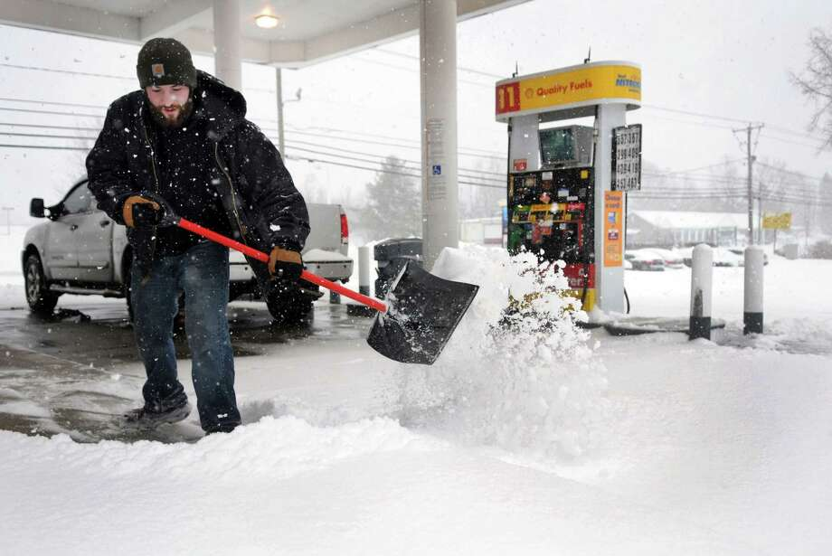 Casey Kiszka, 25, with Preferred Lawn Service in New Milford, shovels the walkway at the Shell Station on Federal Road in Brookfield, Conn. during Thursday's snowstorm, Feb. 13, 2014. Photo: Carol Kaliff / The News-Times