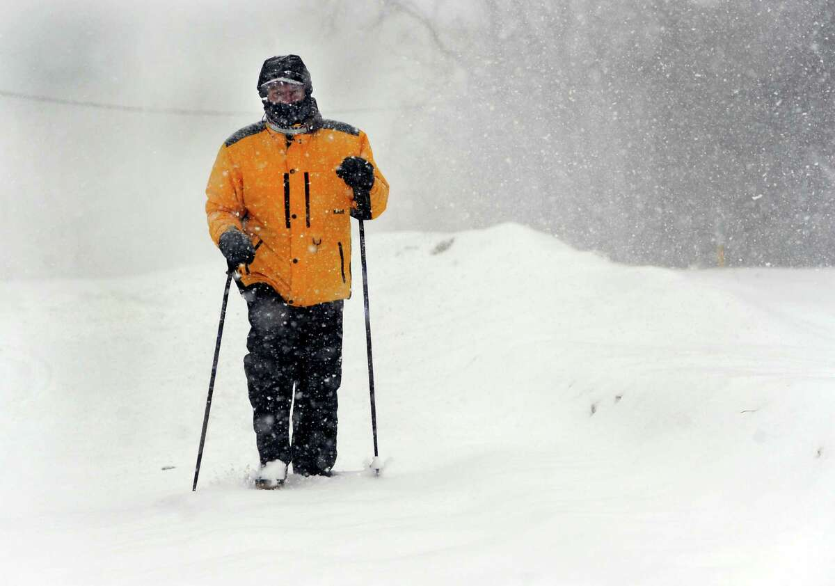 Tom Strang, 62, walks in the falling snow on Old Brookfield Road in Danbury, Conn. Thursday, Feb.13, 2014.