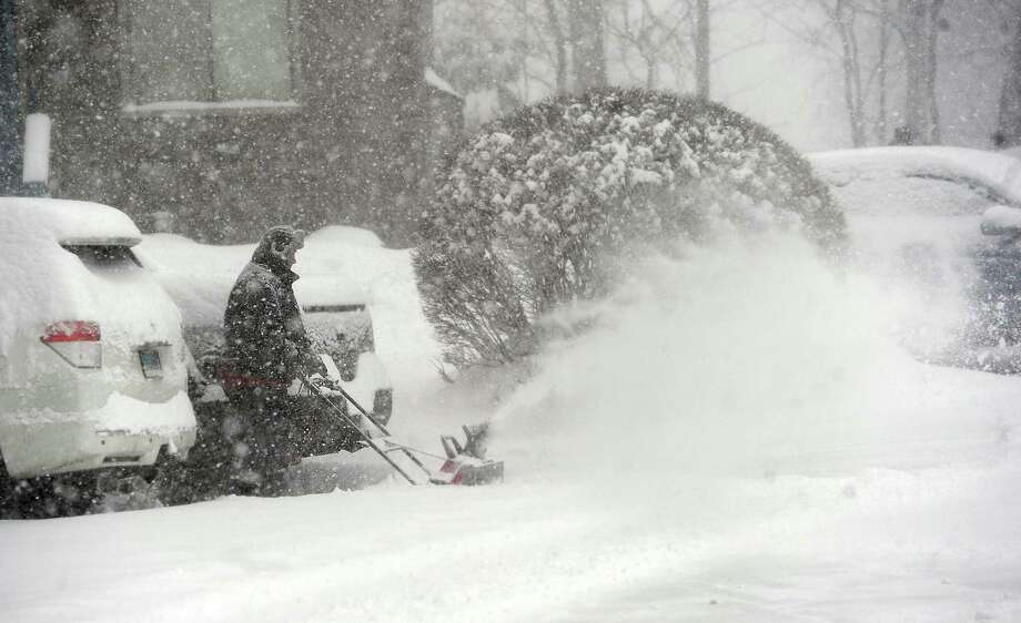 A man clears snow from the driveway of Shepherd Hill Condominiums in Danbury, Conn., during Thursday's snow storm, Feb. 13, 2014. Photo: Carol Kaliff / The News-Times
