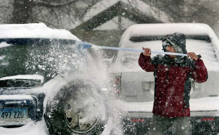 George Coelho, 35, clears snow from his car on James Street in Danbury, Conn., Thursday, Feb. 13, 2014. Photo: Carol Kaliff / The News-Times