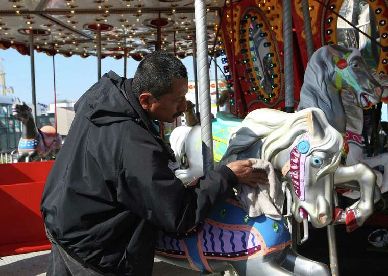 Mario De La Cruz Perez cleans one of the carousel animals that is part of the carnival at the San An