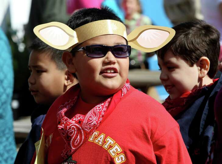 Gilbert Flores, 8, wears a set of paper cow ears as he stands in line for the Petting Zoo at the San