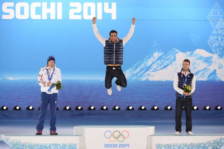 A picture taken with a robotic camera shows Czech Republic's silver medalist Ondrej Moravec, France's gold medalist Martin Fourcade and France's bronze medalist Jean Guillaume Beatrix celebrating on the podium during the Men's Biathlon 12.5 km Pursuit Medal Ceremony. Photo: ANTONIN THUILLIER, AFP/Getty Images