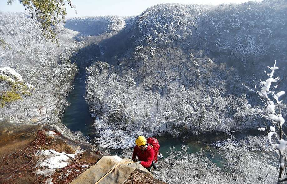 February white abseil:Israel Partridge of True Adventure Sports prepares to rappel into the snow- and ice-covered Little River Canyon near Fort Payne, Ala. A winter storm dropped as much as a foot of snow on parts of northern Alabama over two days. Photo: Hal Yeager, Associated Press