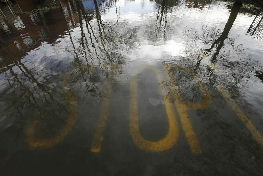 Underwater warning: In Egham, England, a stop sign sits under several inches of water after the River Thames overflowed its banks. Photo: Sang Tan, Associated Press