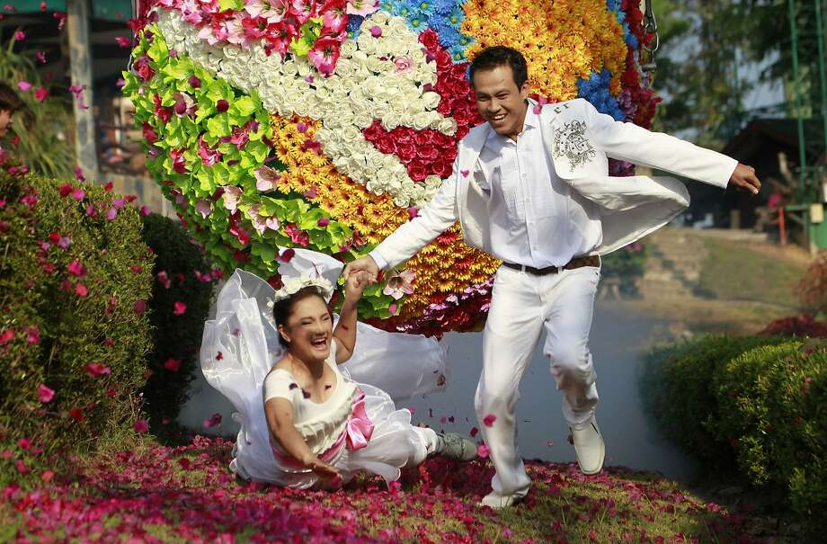 Thai groom Wichan Vina, 32, right, holds the hand of his bride Wilailuk Roongros, 31, who fell on the ground as the both run from a giant ball decorated with flowers, called Run Way of Love, in Prachinburi province, eastern Thailand Thursday, Feb. 13, 2014. They celebrated their wedding on the eve of St. Valentine's Day. (AP Photo/Wason Wanichakorn) Photo: Wason Wanichakorn, Associated Press
