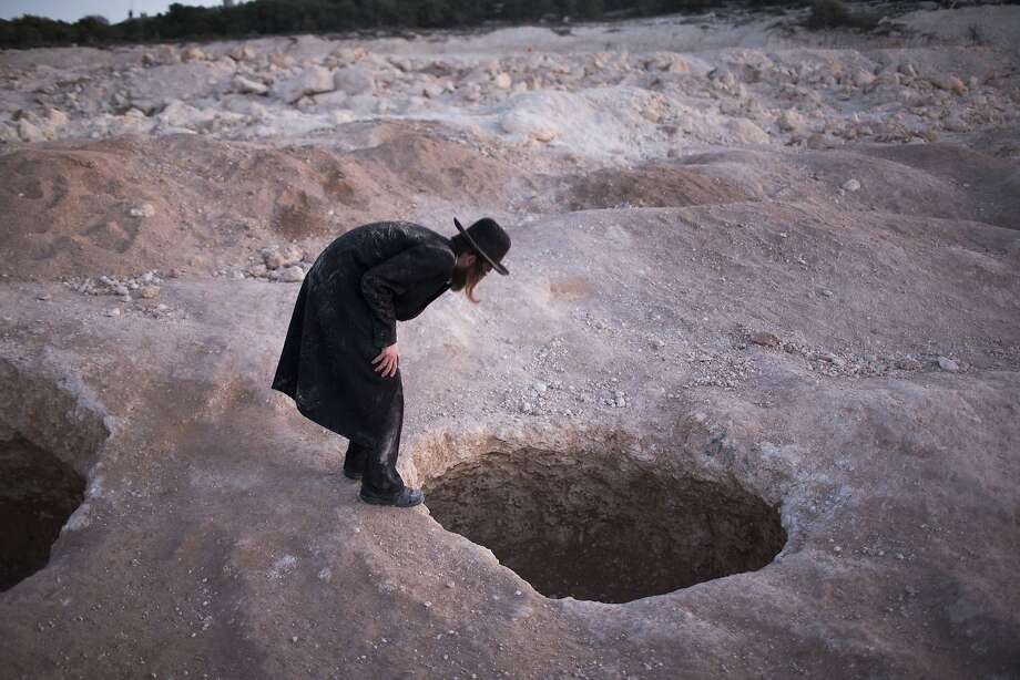 Bones of contention: An Ultra Orthodox man peers into a cavern opening during a protest against construction in the town of Bet-Shemesh, Israel. The site is believed to contain ancient graves inside the caves. Photo: Ilia Yefimovich, Getty Images