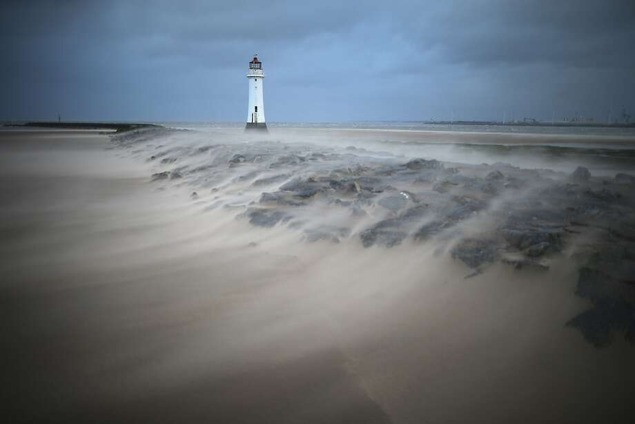High winds whip sand over the breakwater next to the Perch Rock lighthouse in New Brighton, United Kingdom. Photo: Christopher Furlong, Getty Images