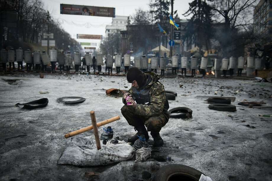 Ukraine at a cross roads: An anti-government protester lights a candle in front of a line of riot police in Kiev. Photo: Martin Bureau, AFP/Getty Images