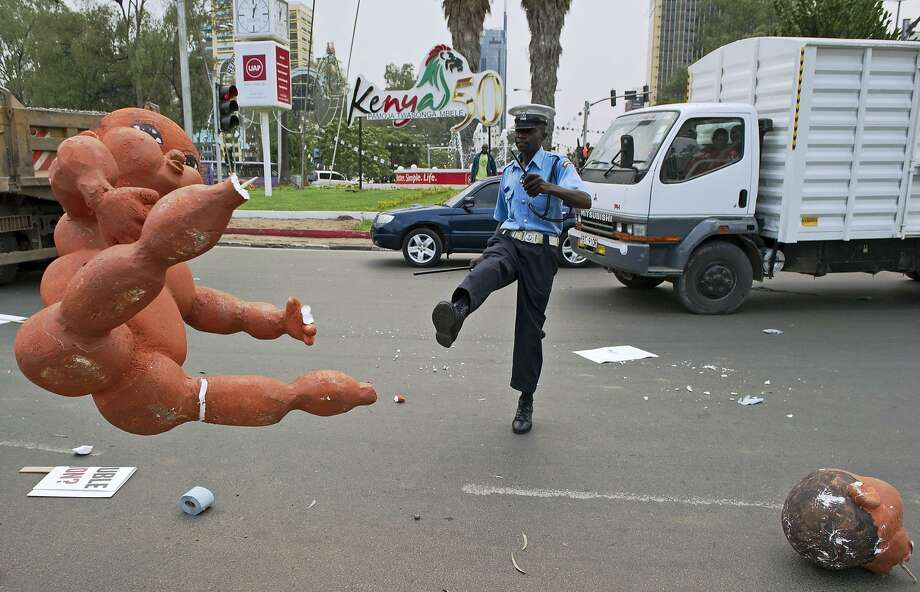 """Volley of the dolls:After dispersing demonstrators, a Nairobi policeman punts a foam effigy of a baby left by a protester. Police used tear gas to break up a """"State of the Nation"""" rally against government corruption, lack of safety in public places, high unemployment and poverty. Photo: Carl De Souza, AFP/Getty Images"""