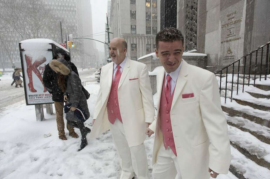 Married in Manhattan:Falling flakes greet newlyweds Steve Cosh and Thiago Cardoso as they walk out of New York's municipal marriage bureau. Photo: Mark Lennihan, Associated Press