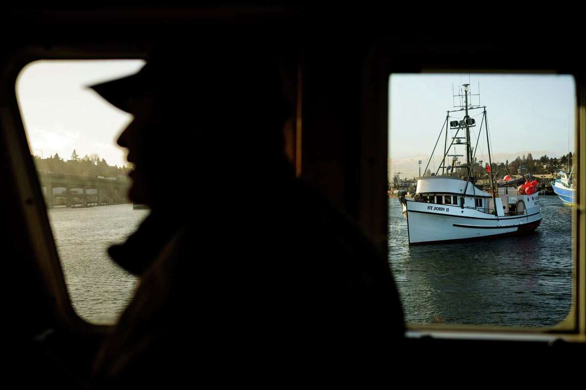 Captain Wade Bassi, left, one of two owners of the halibut and black cod ship, Polaris, watches from his window during the Parade of Historic Fishing Schooners Thursday, Feb. 13, 2014, beginning at Fishermen's Terminal and concluding at MOHAI in Seattle. The eight-boat parade consisted only of operational historic wooden fishing schooners - some more than 100 years old - responsible for seafood on dinner tables nationwide.