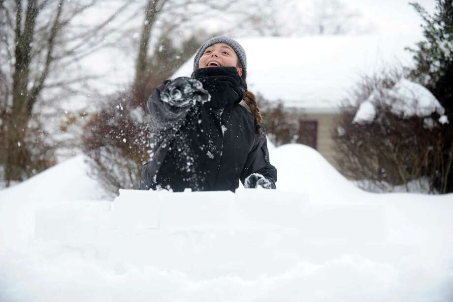Hannah Kozdeba, 13, of Trumbull, throws snowballs from behind a fortress of snow Thursday, Feb. 13, 2014, during a battle at her cousin's house in Shelton, Conn. Photo: Autumn Driscoll / Connecticut Post