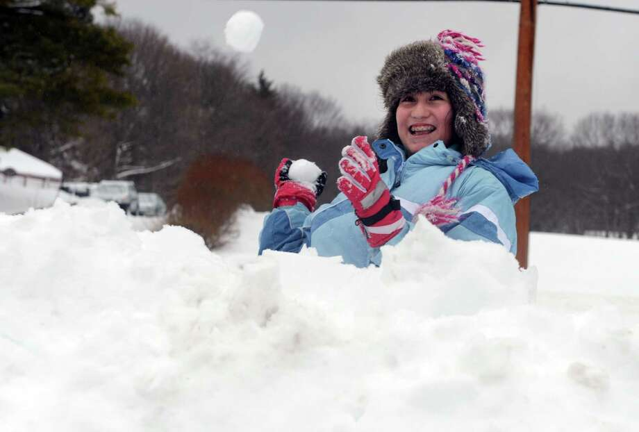 Zoë Figueroa, 13, throws snowballs from behind a fortress of snow Thursday, Feb. 13, 2014, during a battle with her cousin in Shelton, Conn. Photo: Autumn Driscoll / Connecticut Post