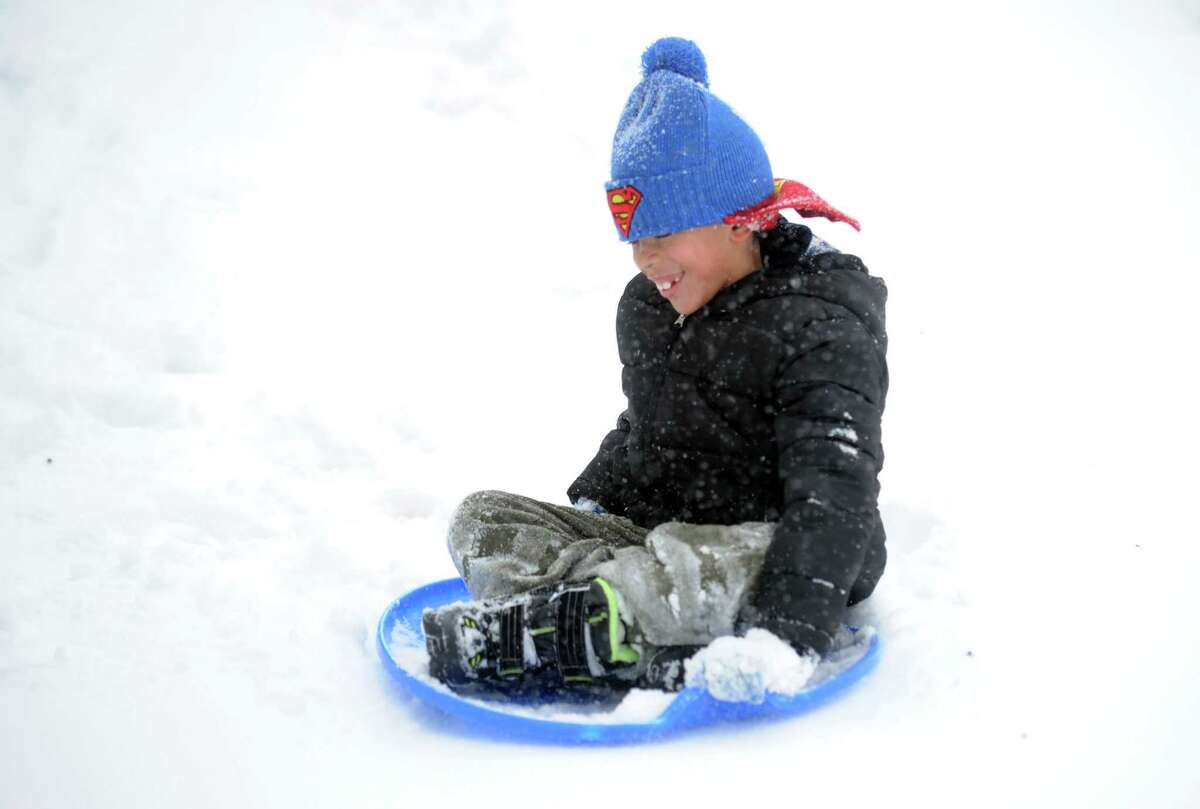 Seven-year-old Romeo Charles sleds down a driveway near his home Thursday, Feb. 13, 2014, in Derby, Conn.