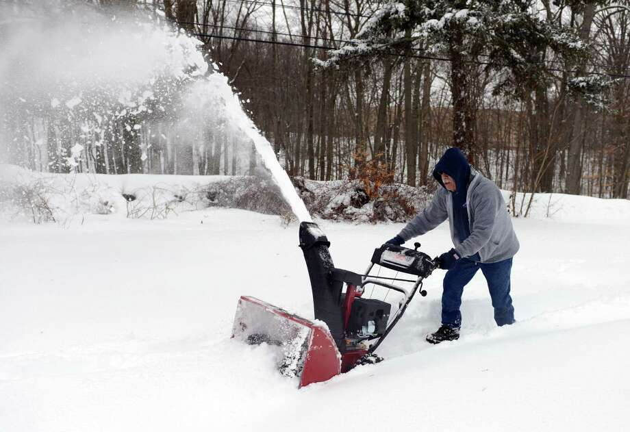 Nick Ross uses a snowblower to clear a path in front of him home Thursday, Feb. 13, 2014, in Shelton, Conn. Photo: Autumn Driscoll / Connecticut Post