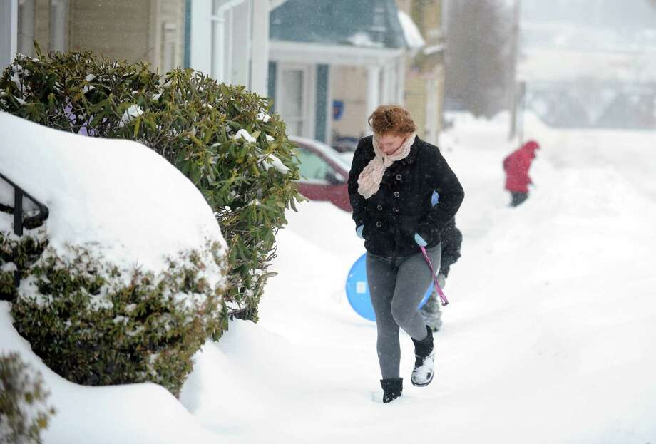 Elizabeth Parsons, of Derby, braces against the cold as she walks up Olivia Street Thursday, Feb. 13, 2014, in Derby, Conn. Photo: Autumn Driscoll / Connecticut Post