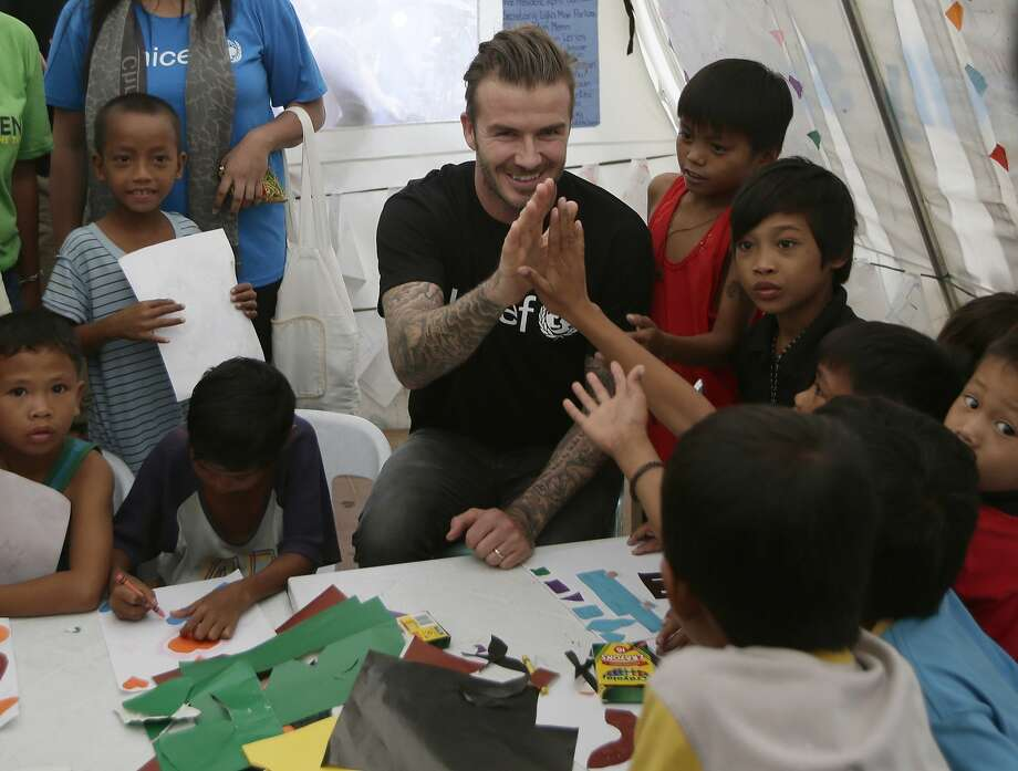 David Beckham, interacting with Filipino typhoon survivors Thursday, plans to bring soccer to Miami. Photo: Bullit Marquez, Associated Press