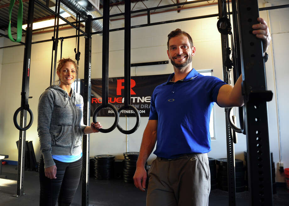 Synergy of Sport Fairfield owners Chris and Meg Skelton pose at their new facility in Fairfield, Conn. on Wednesday January 22, 2014. Chris is a chiropractor who combines chiropractic care with CrossFit training for his clients. Photo: Christian Abraham / Connecticut Post
