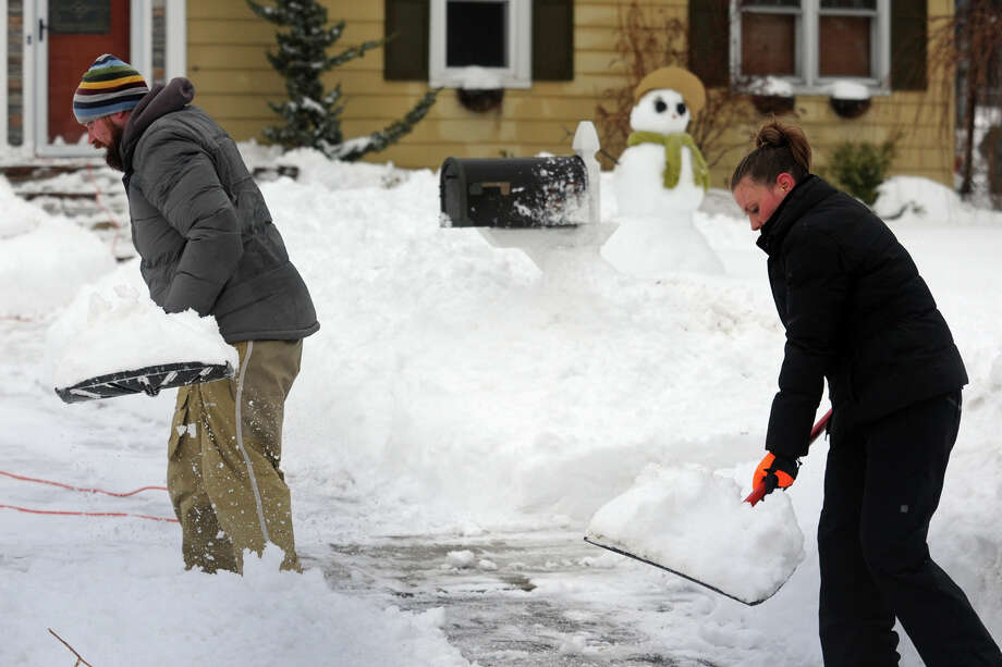 Matt and Michelle Azwoysky clean up following a heavy snow in Stratford, Conn. Feb. 13, 2014. Photo: Ned Gerard / Connecticut Post