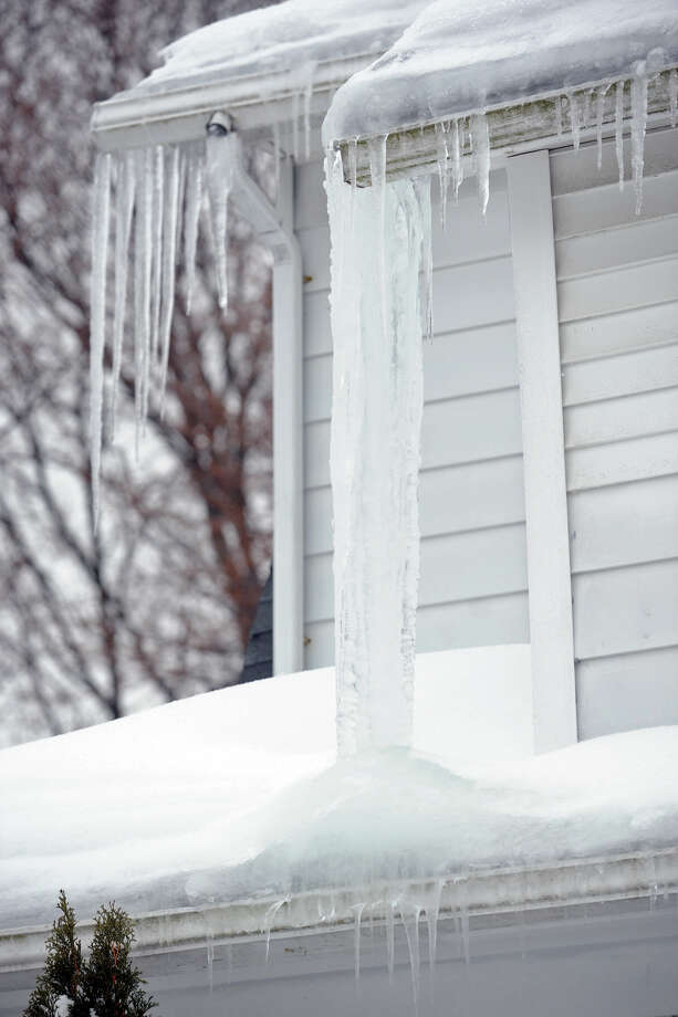 Icicles form from a home following a heavy snow in Stratford, Conn. Feb. 13, 2014. Photo: Ned Gerard / Connecticut Post