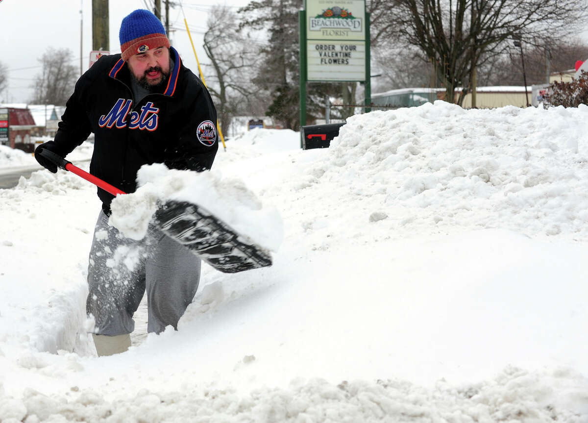 Paul Olenski shovels snow at his father's house on New Haven Avenue in Milford, Conn. on Thursday February 13, 2014.