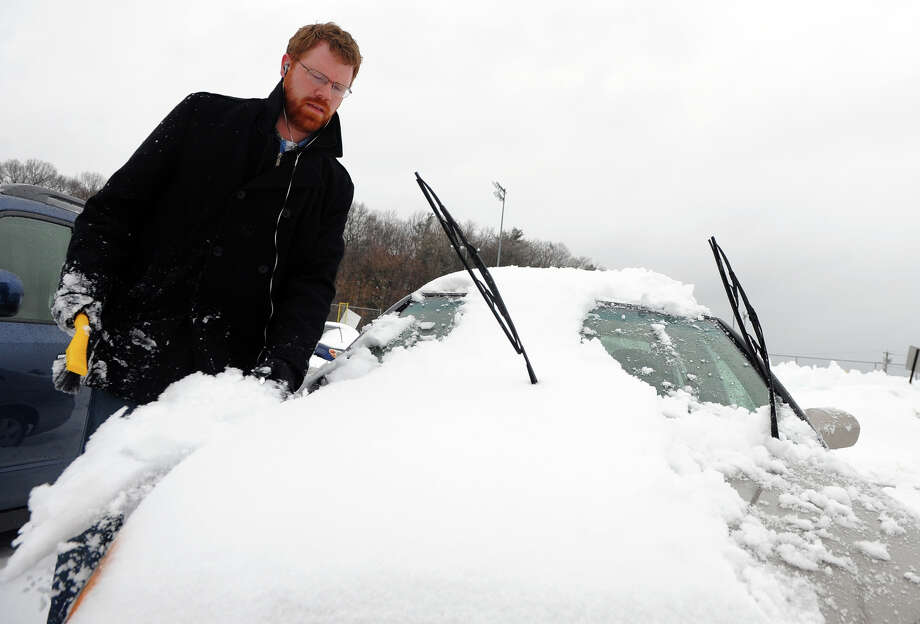 Chris Hein, of Milford, cleans the snow off his car after work in Milford, Conn. on Thursday February 13, 2014. Photo: Christian Abraham / Connecticut Post