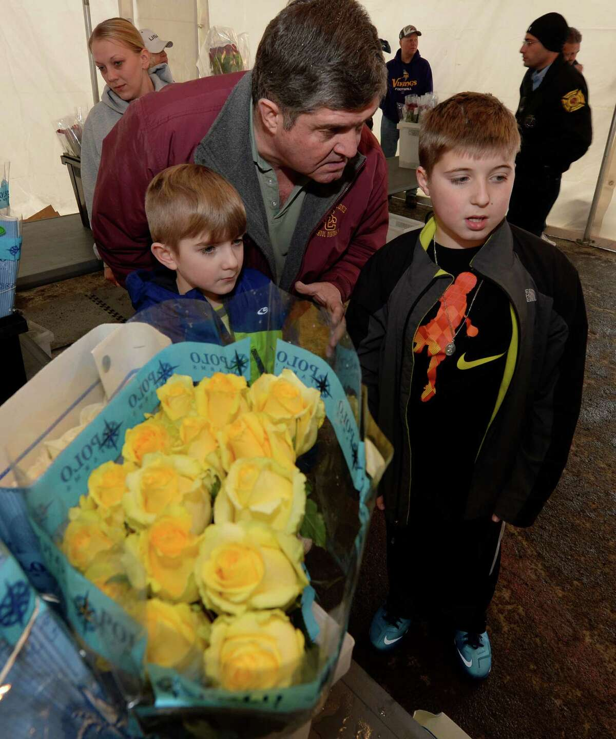 Grandfather Brian Casey give guidance to his grandson's Luke Tarpay, 8, left, and Casey, 12, who were buying roses for their mother Cori Tarpay during the Colonie Fire Department's annual Valentine's Rose Sale Thursday morning, Feb. 13, 2014, in Colonie, N.Y. The Colonie Fire Company uses the rose sale as a benefit for the fire company. (Skip Dickstein / Times Union)