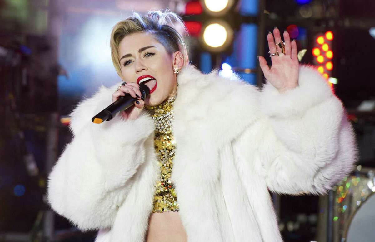 In this Dec. 31, 2013 file photo, Miley Cyrus performs in Times Square during New Year's Eve celebrations in New York. Cyrus is kicking off her North American ôBangerzö tour Feb. 14, 2014, in Vancouver. ôRen and Stimpyö creator John Kricfalusi and LA contemporary artist Ben Jones have crafted videos to play during the 38 shows as Cyrus prioritizes singing over dance routines. (Photo by Charles Sykes/Invision/AP, File)