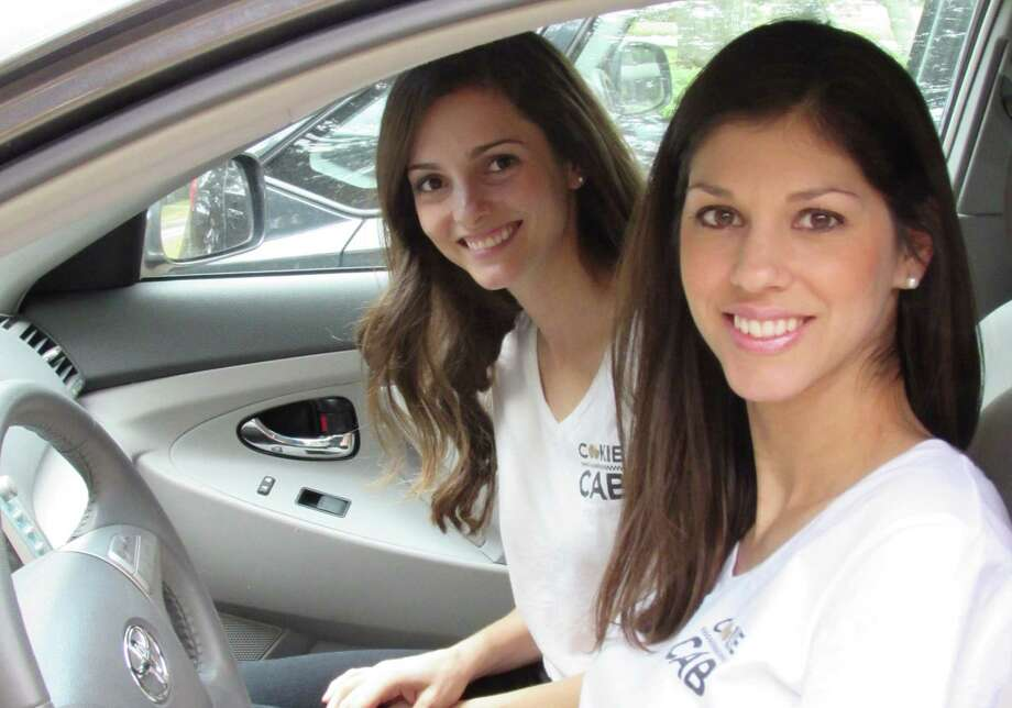 Molly Rodenberg (left) and Lauren Pepping run the Cookie Cab, selling and delivering fresh, warm cookies around town. Photo: Burt Henry / San Antonio Express-News