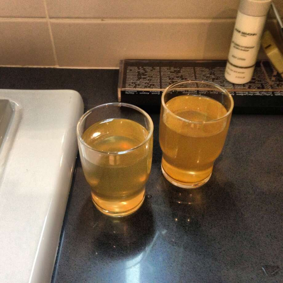 Don't drink the water please. Drinking glasses show yellow-colored water poured from a bathroom faucet at a Sochi. It was just one of many complaints that rolled in once the media arrived at Sochi's barely ready hotels. (Stacy St. Clair/Chicago Tribune) Photo: Stacy St. Clair, McClatchy-Tribune News Service