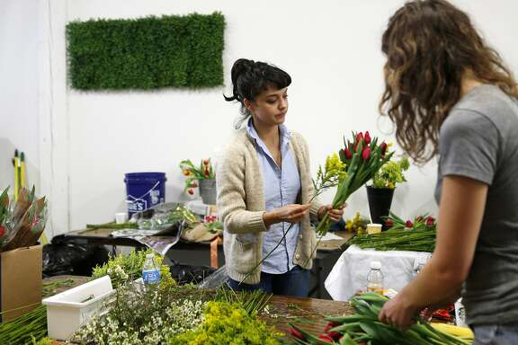 Freelance florist Taj Robinson assembles a bouquet to be delivered by bike messengers for BloomThat on Thursday, February 13, 2014 in San Francisco, Calif.
