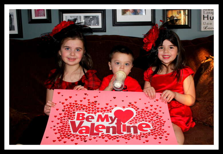 In true Valentines Day spirit, sisters Brianna and Brooke giving their baby brother Bryce some Valen