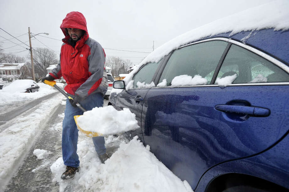 Juned Kastura clears snow from around his car during the snow storm in Stamford, Conn., on Thursday, Feb. 13, 2014. Photo: Jason Rearick / Stamford Advocate