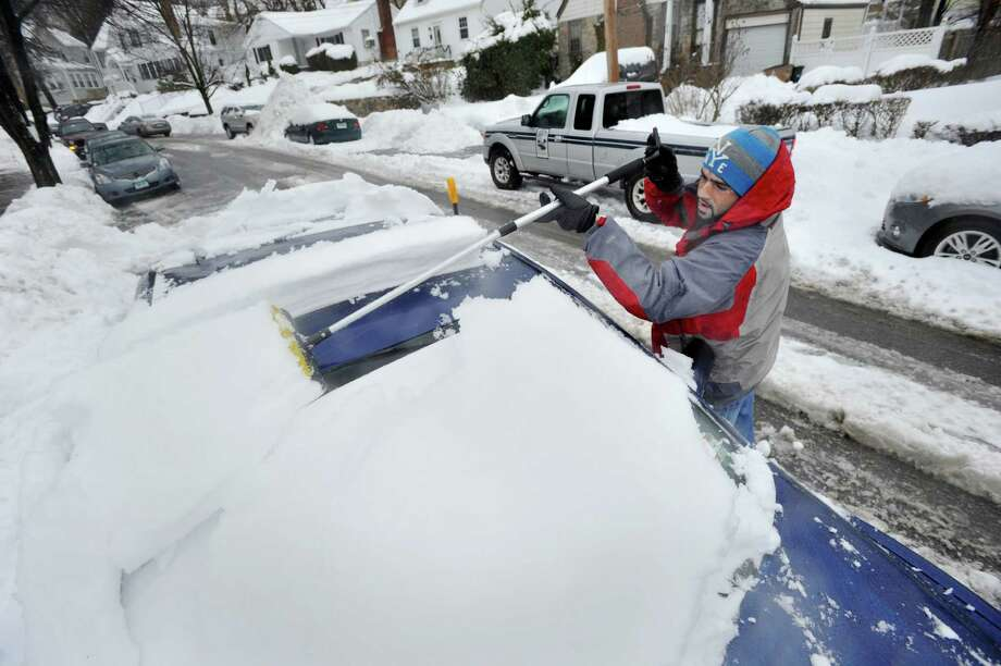 Juned Kastura clears snow from the top of his car during the snow storm in Stamford, Conn., on Thursday, Feb. 13, 2014. Photo: Jason Rearick / Stamford Advocate