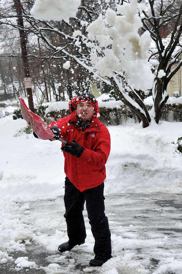 Anllely Mejia clears snow from his driveway during the snow storm in Stamford, Conn., on Thursday, Feb. 13, 2014. Photo: Jason Rearick / Stamford Advocate