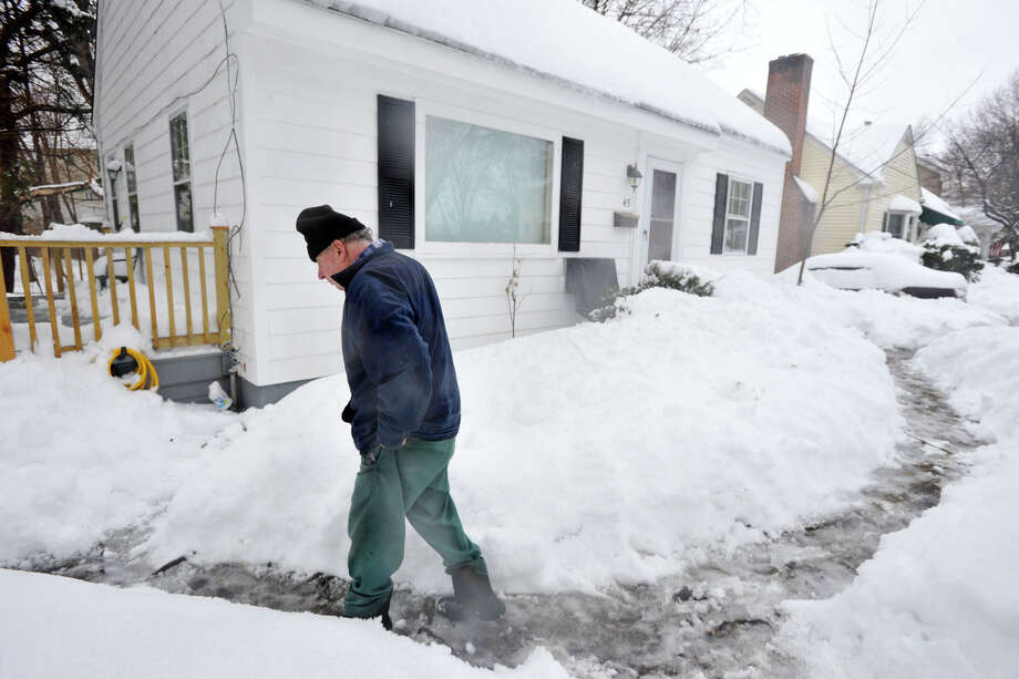 Vito Bova walks back to his house after laying seed in his front yard for the neighborhood birds during the snow storm in Stamford, Conn., on Thursday, Feb. 13, 2014. Photo: Jason Rearick / Stamford Advocate
