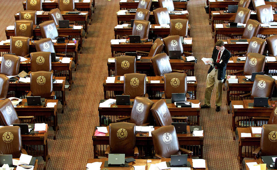 A member of the Sergeant at Arms, Jack Adams, places updated resolutions on the empty desks of House Representatives at the State Capitol on Sunday, May 26, 2013, in Austin, Texas. Members of the House of Representatives left the chamber to gather in their respective caucuses before returning to continue the 83rd Legislature.  (AP Photo/Austin American-Statesman, Rodolfo Gonzalez) Photo: Rodolfo Gonzalez, MBO / Austin American-Statesman