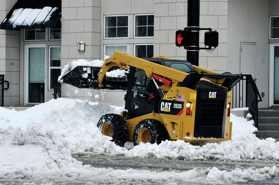 A small front-end bucket loader clears snow on the south end of Washington Boulevard during the snow storm in Stamford, Conn., on Thursday, Feb. 13, 2014. Photo: Jason Rearick / Stamford Advocate