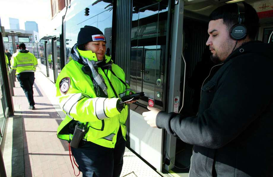 Metro fare inspector Toilicia Caldwell checks a passenger's Q Fare card. Passengers should expect to see more of these inspections as new lines open. Photo: Melissa Phillip, Staff / © 2014  Houston Chronicle