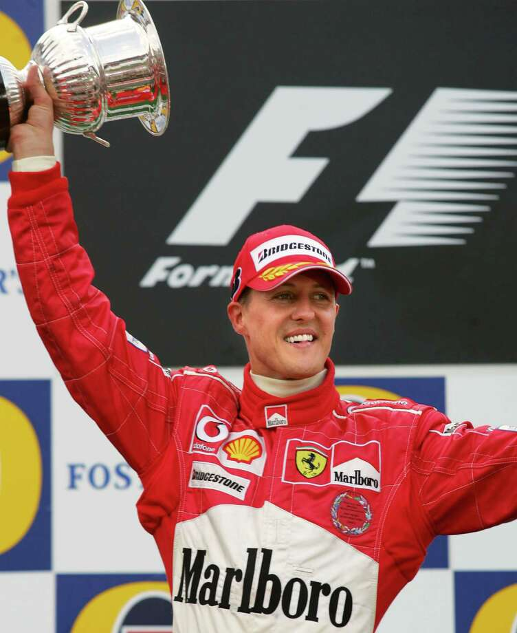 (FILES) - A photo taken on August 29, 2004 shows Ferrari's German driver Michael Schumacher holding his trophy on the podium of the Spa-Francorchamps racetrack after winning the Belgium Grand Prix, in Francorchamps, Belgium, and his fith consecutive driver's championship title, the seventh and final of his career. Michael Schumacher, the retired seven-time Formula One champion who often braved death on the tracks, remained in a critical condition on December 30, 2013 after an off-piste skiing accident in the French Alps. The German racing legend, who turns 45 at the end of the week, had been skiing off-piste on December 29, 2013 with his 14-year-old son in the upmarket Meribel resort when he fell and hit his head on a rock, prompting an urgent evacuation by helicopter. AFP PHOTO DENIS CHARLETDENIS CHARLET/AFP/Getty Images ORG XMIT: - Photo: DENIS CHARLET / 2004 AFP